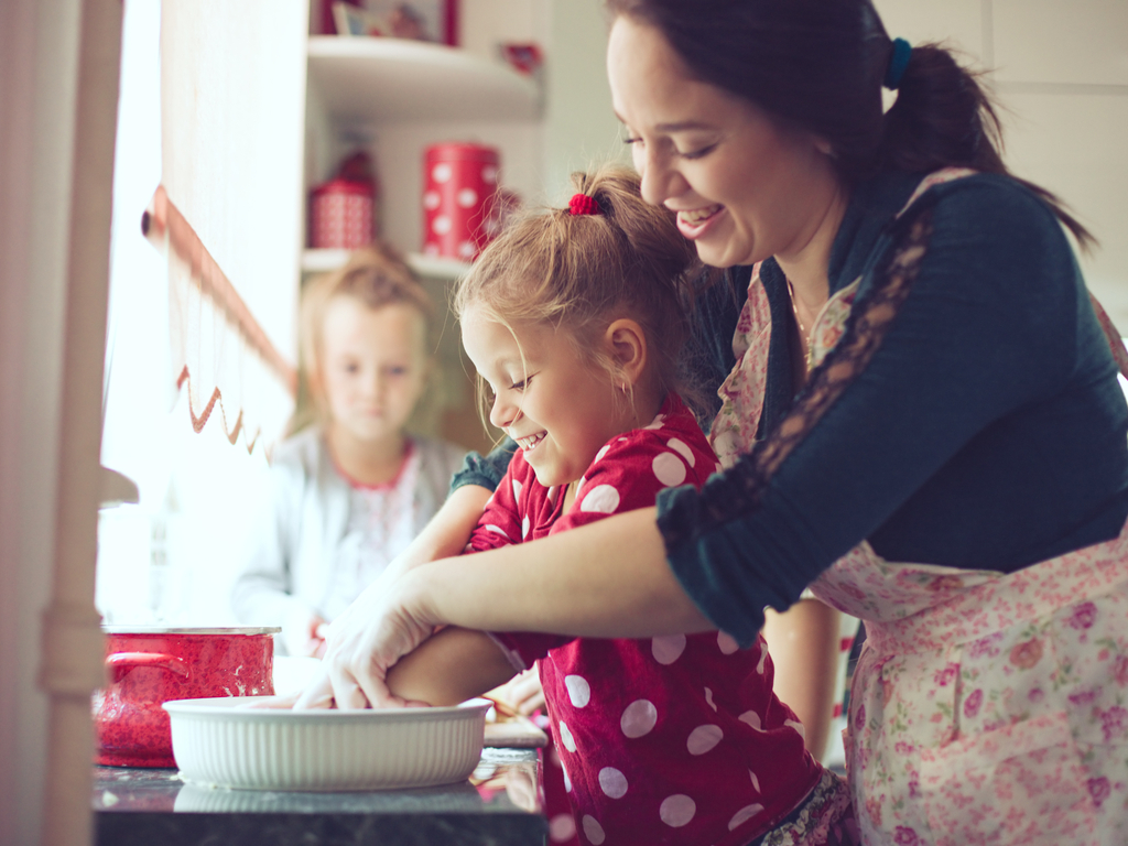 mother cooking at home with her daughter