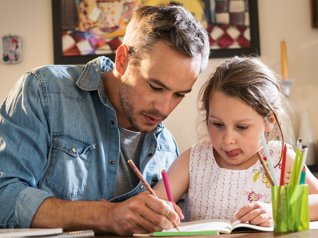 father helps daughter with her homework